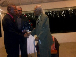 Prime Minister Tillman Thomas handing over the congratulatory plaque to Sir John